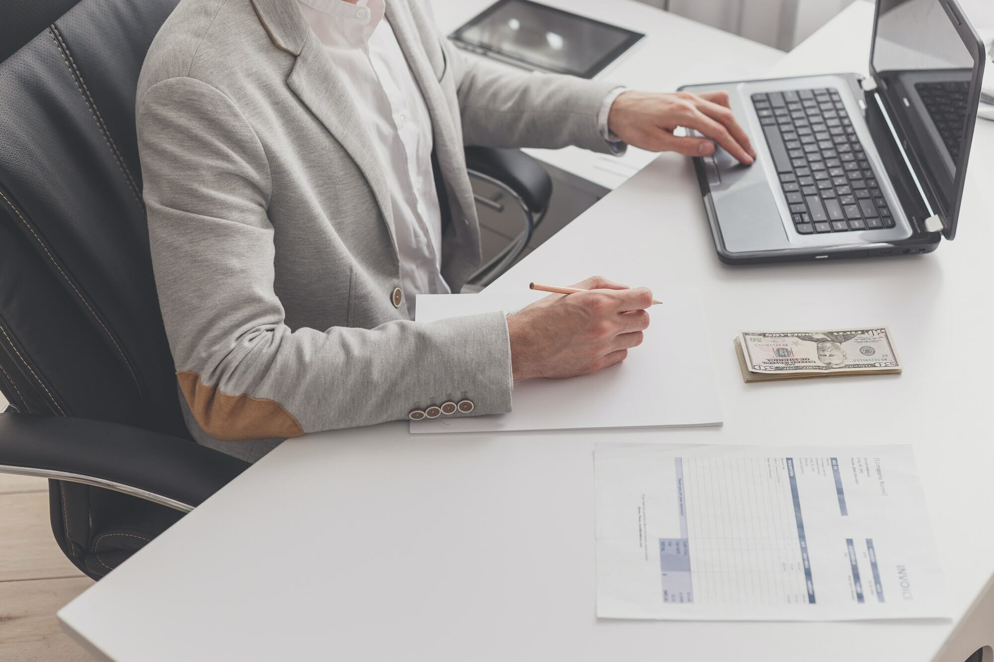 A male accountant works at a pc in an office at home.