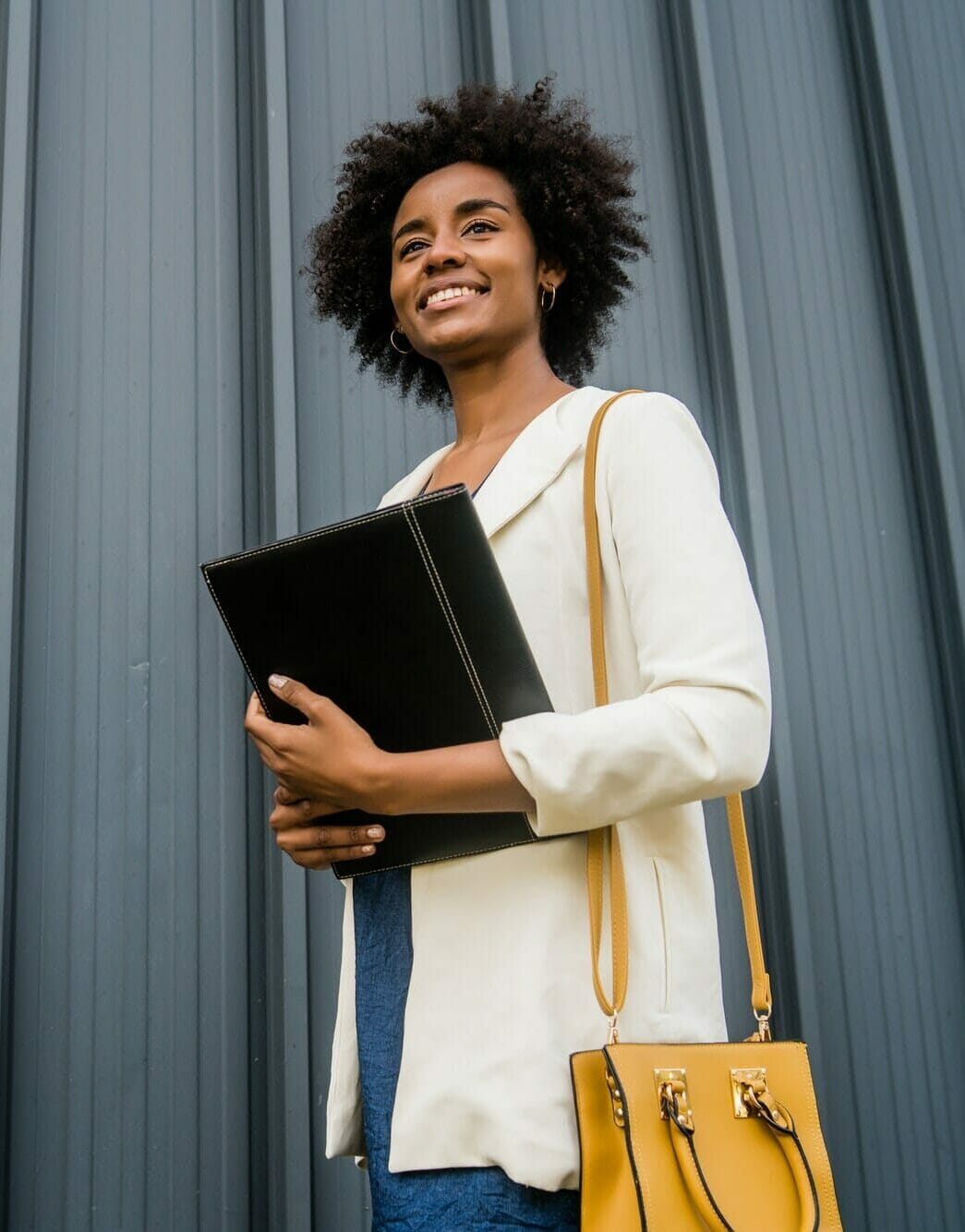 Afro businesswoman holding clipboard outdoors at the street.
